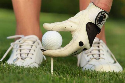Bild Hand im Golfhandschuh teet einen Golfball auf